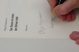 Olga Grjasnowa signiert ein Papierbuch auf der Leipziger Buchmesse 2012   Copyright: Das blaue Sofa / Club Bertelsmann.
